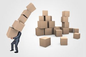 a businessman carrying five boxes, with a dozen moving boxes behind hime