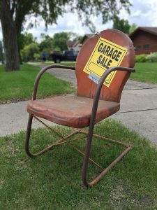 a garage sale sign on an old brown chair in the backyard