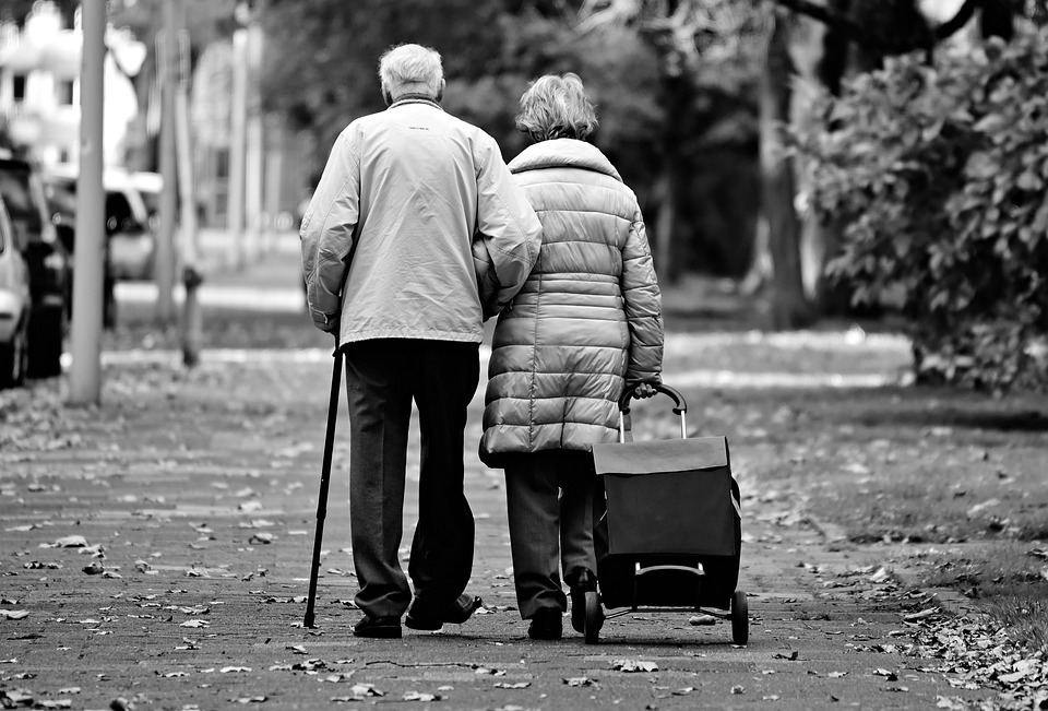An elderly couple walking down the street.