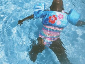 A toddler wearing blue floral pool float in a swimming pool