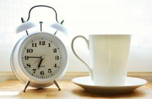A white mug next to a white alarm clock.