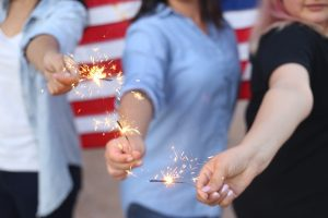 Three women holding sparklers.