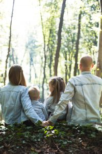 Image of a family sitting in the woods