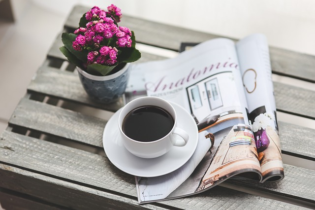 a coffee, a magazine and a plant