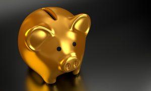 a golden piggy bank standing on a dark surface
