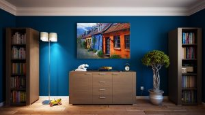a room with a blue wall, a painting, a lamp, wardrobe and flowers