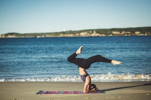 A woman doing yoga by the ocean