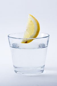 a glass of water with lemon in it